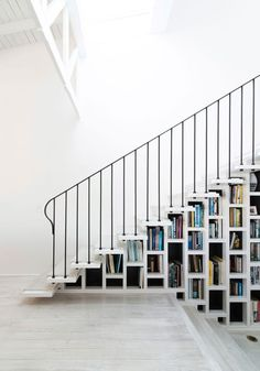 Limed timber stair treads on the staircase, and matching limed original timber floorboards weave together consistently through the spaces as if they had always been there.   A book filled bookshelf is nestled between the studs of a wall supporting the staircase.