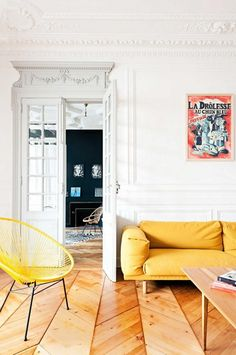 All white walls with detailed moldings, french doors, a yellow sofa and chair, a light wood coffee table, and wall art.