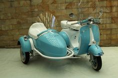 Beautiful blue scooter with a sidecar...... I have always wanted one of these.