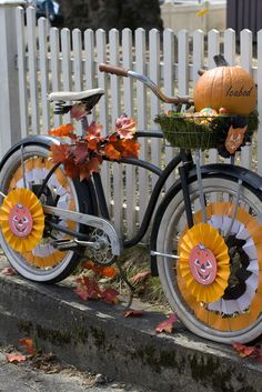 Layer a black vintage bike's wire basket with sheet moss & add a pumpkin! (or small gourds) Use white, black, and orange streamers to weave through the spokes of the tires and a circle of pleated scrapbook paper and stickers to fashion the Halloween pinwheels that adorn the wheels and bicycle basket.