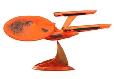 "Star Trek USS Enterprise NCC-1701 ""Final Flight"" Starship This translucent rendering of the Enterprise is meant to replicate its fiery last flight down to the Genesis planet, after self-destructing in orbit. The ship measures approximately 14 inches long, and includes a display stand. It comes in commemorative window packaging. Limited to only 400 pieces. Booth #2607 $65.00"