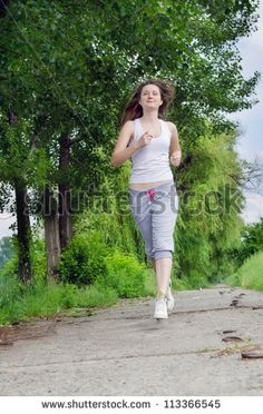 Young woman in casual clothes jogging along a path through a park as she takes her daily exercise to keep fit - stock photo