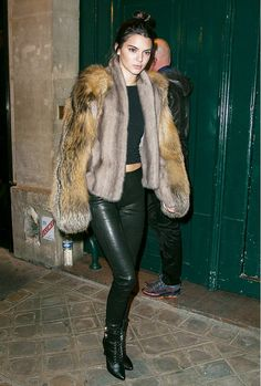 Kendall Jenner wears a fur coat with black leather pants and black ankle boots.