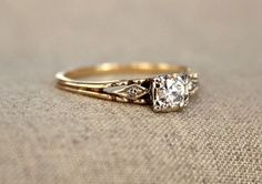 Three Stone Art Deco Diamond Engagement Ring | This tapered gold band gives way to holding this gorgeous diamond center stone with geometric details adorning each side. This luxe vintage ring is so romantic and perfect for the old-fashioned bride who wants everything about her wedding look to be classic and timeless.