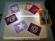 Teaching 2 and 3 Year Olds: Using the light table in the writing area with stencils.