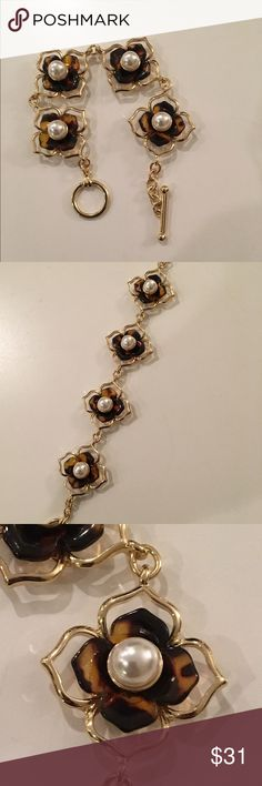 Gorgeous tortoise shell flower bracelet This gorgeous bracelet is made of faux tortoise flowers centered with white pearls in a gold bracelet with a gorgeous toggle closure. Jewelry Bracelets