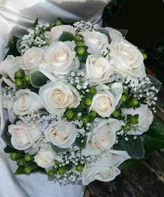 Brudebuketten består af roser, brudeslør og grønne bær