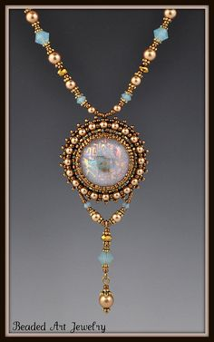 I created this piece using one of my fused Dicrhoic glass cabochons for the center and bead embroidered around it with seed beads and Swarovski pearls. A tassel is attached using Swarovski pearls, Pacific Opal crystals, Gold Chineses crystal, bead caps and heishi. The necklace is