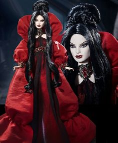 "Haunted Beauty Vampire™ Barbie® Doll  Designed by: Bill Greening  The Haunted Beauty Vampire™ Barbie® doll wears a red charmeuse and black chiffon gown. Elaborate jeweled accents are featured at the neck highlighted by red and gold trim on the empire waist. Her gothic-inspired red shantung coat with a face-framing collar and full sleeves adds a dramatic touch. Her raven hair, pale skin, crimson lips and delicate white ""fangs"" will leave you utterly enchanted."
