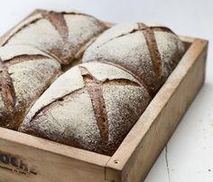 Grovt byggbrød er saftig og godt i matpakken eller til lunsj. Oppskriften med byggmel, fullkornshvetemel og sirup gir fire brød bakt i langpanne.