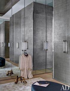 A chic master bedroom closet has palladium-leaf doors