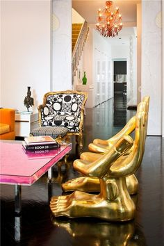 Pink accent table with black and white grphic print chair and gold hand and foot-shaped chairs by Jonathan Adler