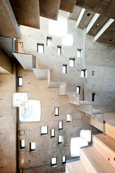 Interior shot of a skinny Japanese house featuring tiny windows and a concrete staircase.