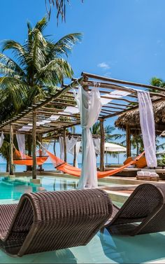 A beachfront infinity pool is decked out with overwater hammocks and cabana beds.