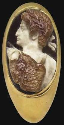 A ROMAN SARDONYX CAMEO OF AUGUSTUS, CIRCA EARLY 1ST CENTURY A.D. Sculpted in three layers, brown on white, on a dark brown ground, with a bust of the Emperor in three-quarter back view. 1 in. (2.5 cm.) wide. (Sale 2450 Antiquities, 2011). -Christie's-