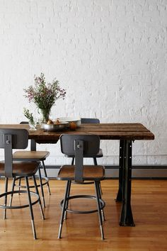 The industrial vibe is softened by informal floral arrangements and whimsical motifs.