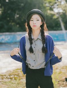 Plaid shirt with a blue cardigan and skinny jeans with suspenders and a hat