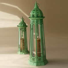 """The """"Alexandrie"""" Verdigris Iron Lanterns Set of Two by Tozai Home® is perfect for any indoor or outdoor space. These floor lanterns are made out of sturdy green iron and glass. Each lantern has an easy open glass door so you can place your candle inside. Both lanterns have distinctive openings on them allowing light and air to escape all parts of the lantern. Candles not included with set."""