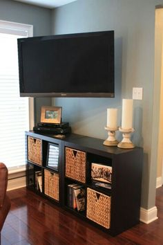 I have this bookcase. Wonder if it would fit between the windows and we could put one of our TVs on the wall and angle at living room?