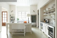 white kitchen- love... glass door fridge for drinks, bar with loveseat stool, shelves instead of cabinet storage, what i can only guess is a farm house sink with huge windows!!!
