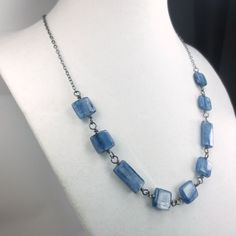 Silvery blue square and rectangle Kyanite beads are wired together in a row of gemstones that will drape along your collar bone. The gemstones are attached to fine chain, making this necklace 19.5 in length. A 1/2 (12mm) lobster clasp closes onto ...