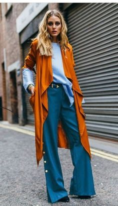 The small details of this outfit make it stand out and make me want to be her anyway. The small buttons on the side of the pants, the slouching pale blue sweater and the pumpkin duster adds a pop of clothing color.