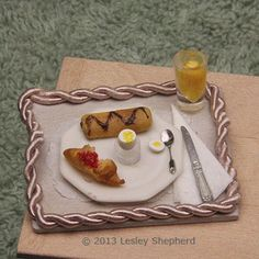 Breakfast tray in dollhouse scale with juice glass, egg in egg cup and croissants.