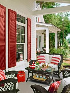 Red accents and classic wicker make this outdoor room a real conversation starter