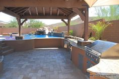 Daytime view. Steps lead to the pool. Open area for a table. BBQ under the shade of a ramada, with ceiling fan.