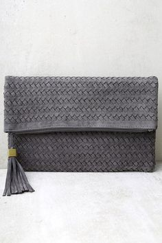 """Get your accessory game on point with the Leave it to Me Grey Clutch! Vegan suede forms a cute fold over clutch with a woven design and two magnetic closures. Top zipper (with tassel pull) opens to an interior zipper pocket and side pockets. Carry as a clutch, or attach the matching 47"""" adjustable strap."""
