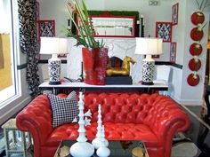 A vintage red leather couch stands out in an eclectic living room, which also has unique red wall vases, a small glass coffee table with three white vases, black and white floral curtains, and a console with matching table lamps.