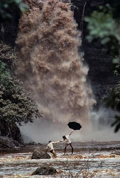 Two men try to cross a monsoon swollen river after the bridge was swept away, Goa, India, ©steve mc curry