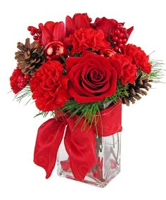 This bouquet is a lovely combination of reds featuring roses, tulips, carnations and mini carnations. The flowers are complimented by fresh greens, pine cones and Christmas balls. All are arranged in a rectangular glass cube with red accent stones at the bottom. Three sizes are available to suit your needs.