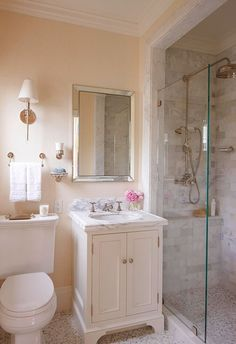 Blush pink walls, marble subway tile and sink surround, and...