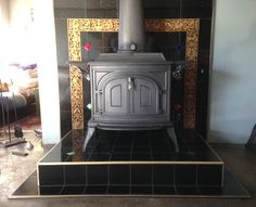 Glass accent tile fireplace surround in black ceramic tile by Uneek Glass Fusions.  www.uneekglassfusions.com