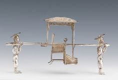 """A Chinese Miniature Silver Palanquin with Two Figures. 4¾""""L x 1¼""""W x 2½""""H  The two standing figures carrying an elaborate filagree sedan chair on two bamboo poles, marked on the underside in Chinese and """"SW,"""""""