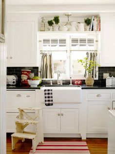 White cabinets with black counter tops and black subway tile back splash. Love the cafe curtains.