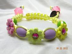 Made with 2mm pale yellow satin cord, features flower buttons with purple & green wooden beads. There is a slip knot with two drawstrings that have pink plastic end beads.    ITEM #: CAAB22    PRICE: $10