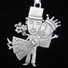 "Leandra Drumm Wedding Couple Ornament  A favorite add-on to include when giving a wedding gift, the Leandra Drumm Wedding Couple is a fun and delightful way to commemorate ""I do's"". A bride is carried by a groom in a top hat as the happy couple waves to all who celebrate their love."