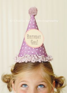 birthday girl...a little girl with eyes focused upward toward her party hat evokes the excitement of her special day