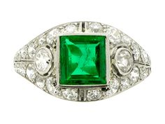 Art Deco emerald and diamond ring, American, circa 1930. A platinum and iridium ring set with one central square step cut emerald in a millegrain collet setting with an approximate weight of 1.00 carats, flanked by two round old cut diamonds in millegrain collet settings with pierced surrounds with an approximate total weight of 0.30 carats, all set within a pierced curved frame with integrated shoulder set with twenty eight round old cut diamonds in bead settings with an approximate total…
