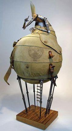"Artist:Greg Brotherton  The Bishop  2010 Size: 30"" x 13 "" x 13 ""  Materials: Welded steel, teak, vintage Boyscout backpack"