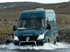 Achleitner Mantra 4x4 Sprinter camper crossing a river in Iceland.
