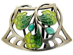 """A good example of an Art Nouveau buckle which has been enamelled in the plique-à-jour method. Plique-à-jour (French for """"letting in daylight"""") is a vitreous enamelling technique where the enamel is applied in cells, similar to cloisonné, but with no backing in the final product, so light can shine through the transparent or translucent enamel. …"""