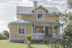 Gult hus, vita fönster, avvikande färg på dörr.