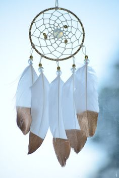 Car Hanging Charm, Car ornament, mini car dream catcher. This small car dream catcher is perfect for anyone who enjoys unique handmade items and would look great hung on your car mirror. This handmade dream catcher measures 3 inches in diameter is made of a gold color metal ring. The web is woven with white cotton thread and a few gold metal beads. The center of the web is accented with large Moonstone bead. Finished with beautiful gold dipped goose feathers attached by clear crystal beads…