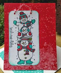 three stacked and smiling snowmen are happy to help you ring in a new year on this handmade card cheery colors of red and teal will brighten up the day for