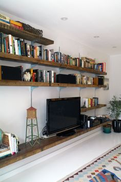 "I love the ""rustic"" (is that the right word?) shelving and how they are storing so many books with the tv.  I like the different lengths of sshelves a lot, too."
