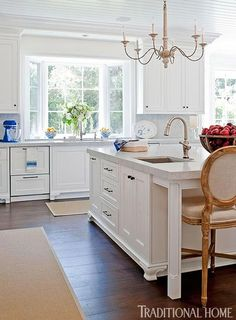 This kitchen's clean white aesthetic is accented with subtle blue and white details - Traditional Home® / Photo: Michael Garland / Design: Lonni Paul
