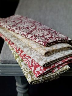 Fermoie -  Fermoie Fabric Collection - A grey table with folds of ornately patterned fabric in white,green, red, grey, gold and burgundy
